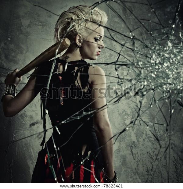 Punk girl with a bat behind broken glass