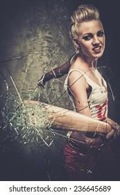 Punk girl breaking glass with a baseball bat