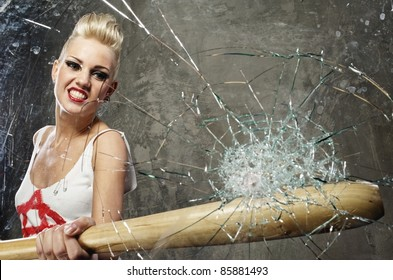 Punk girl breaking glass with a bat