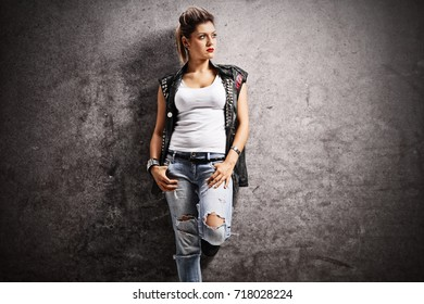 Punk girl leaning against a rusty gray wall and looking away