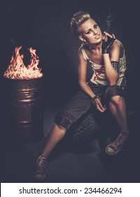 Punk girl smoking a cigarette sitting on a tires