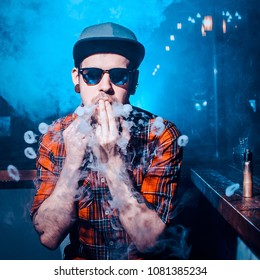 Punk hipster man is smoking a mechanical vape device. Toned image. The concept of popularization of vaping. Vaping man in sunglasses lets out a lot of rings of steam or smoke square cropping