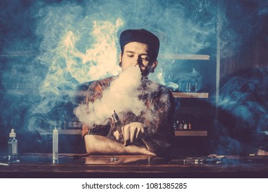 Punk hipster man is smoking a mechanical vape device. Toned image. The concept of popularization of vaping. Ecig rapairing process with cloud of steam horizontal
