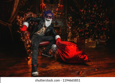 Сheerful punk Santa with a bag of gifts in his hands  in luxurious apartments decorated for Christmas. Bad Santa concept.