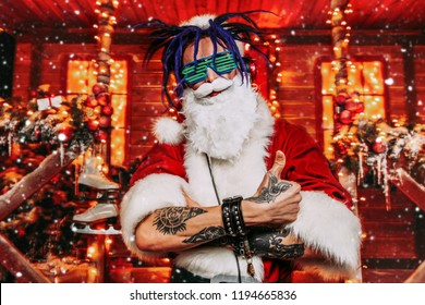 Сrazy punk Santa Claus in luminous glasses and headphones holds a party near his house decorated with lights. Christmas cool party.