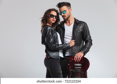 punk woman holding her man by jacket and looks at the camera, rock and roll couple on grey studio background