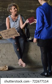 a punk woman sitting under a bridge with bottle of alcohol next by holding a sign and getting pleased a bible from a businesswoman