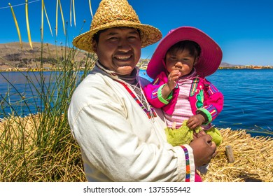 Puno / Peru - 11 04 2018: Local man and his daughter at Uros floating island