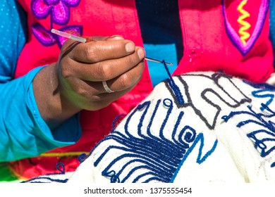 Puno / Peru - 11 04 2018: Local woman embroidering close up