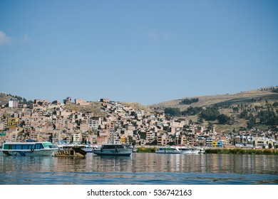 "PUNO, PERU - CIRCA OCTOBER 2016: Boats docked along the shore of lake Titicaca in Puno, Peru. At 3812 meter above sea level, it is the ""highest navigable lake"" in the world."