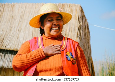 PUNO, PERU - CIRCA OCTOBER 2016: An Uro woman living a floating island made entirely of totora reeds on lake Titicaca in Puno, Peru.