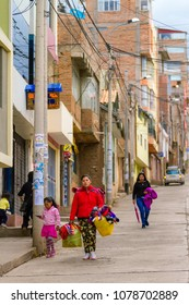 Puno, Peru - February 8, 2018: Textile handicrafts woman walks down a street in Puno along with her daughter to her stall