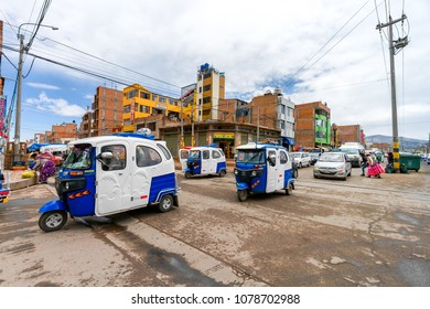 Puno, Peru - February 8, 2018: Dozens of motorcycle taxis cross a street in Puno at noon in the local street market area