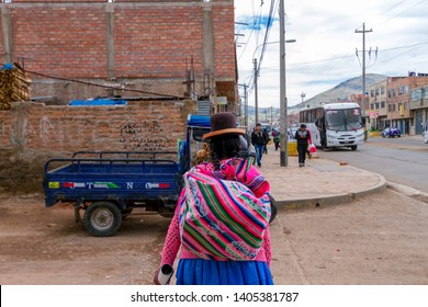 Puno, Peru - February 8, 2018: Woman with typical clothes seen from behind walks through the streets of Puno