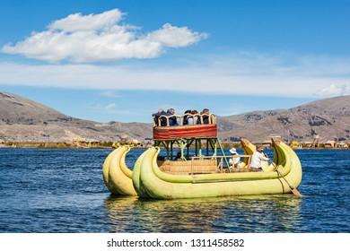 PUNO, PERU - MAY 14, 2015: Unidentified tourists in Totora boat, Titicaca lake near Puno, Peru