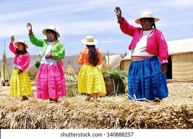 PUNO, PERU - NOV 28: Unidentified women in traditional dresses welcome tourists in Uros Island, Puno, Peru, NOV. 28. 2010.The Uros are a pre-Incan people who live on 42 self-fashioned floating islands