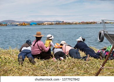 PUNO, PERU - NOVEMBER 5: local people relax in front of water on floating Uros islands at lake Titicaca near Puno, Peru on November 5, 2018