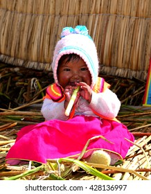 PUNO, PERU - SEPTEMBER 5, 2014: Unidentified small Uro girl  in traditional clothes on the Uros floating island on the Lake Titicaca near Puno, Peru