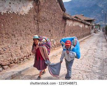 Puno, Peru-20 June, 2016: Puno elders on village streets with old adobe houses carrying husehold items