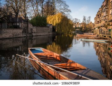 A punt with a punting pole resting on it on the river Cam in Cambridge, England on a sunny spring day. Taken from water level.