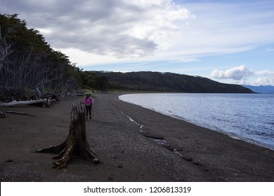 PUNTA ARENAS, CHILE - MARCH 09 2018: an unidentified backpacker walking on a beach between Cabo Froward and San Isidro lighthouse, Punta Arenas, Chile