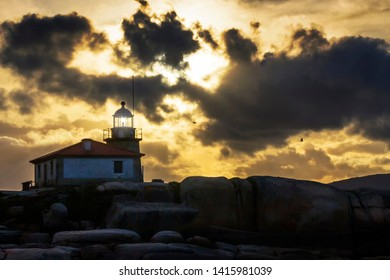Punta Cabalo lighthouse lighting at stormy suntet in Arousa Island, Galicia, Spain