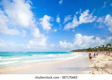 Punta Cana, Dominican republic - January 13, 2015: Coastal Caribbean seascape. Atlantic ocean coast, ordinary tourists walk along sandy beach of Punta Cana resort
