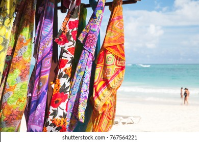 Punta Cana, Dominican Republic - January 4, 2017: Assortment of color scarves hangs on the beach stall counter with Atlantic Ocean coast on a background