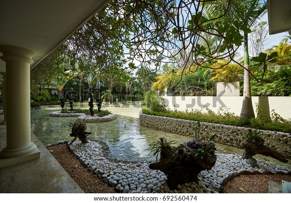 PUNTA CANA, DOMINICAN REPUBLIC - MARCH 19, 2017: Modern tropical island style landscape with pond at Paradisus Hotel in Playa Bavaro in the Caribbean. Visited by tourists from all over the world.