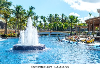 Punta Cana, Dominican Republic - October 26, 2018: People relax in the swimming pool among palm trees in the resort of Punta Cana.