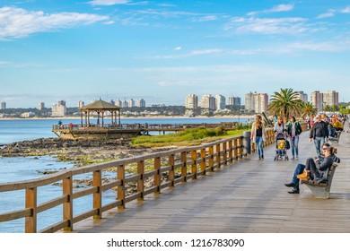 PUNTA DEL ESTE, URUGUAY, OCTOBER - 2018 - People at sunny winter at waterfront boardwalk in punta del este city, Uruguay