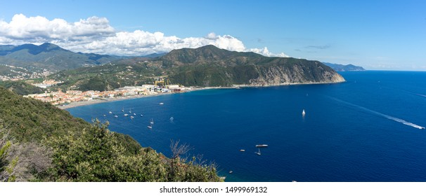 Punta Manara, Sestri Levante, Liguria. Riva Trigoso sea view. Boats and sailboats on blue sea with the background of the Ligurian mountains topped by white clouds