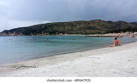 Punta Molentis Beach, Villasimius - 26 Septmber, 2016: uninidentify people on the beach while a black cloud is coming in the sky as editorial