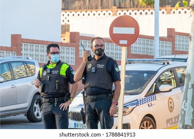 """Punta Umbria, Huelva, Spain - August 2, 2020: Spanish police  with """"Local Police"""" logo emblem on uniform maintain public order in the street Calle Ancha in Punta Umbria, Spain"""