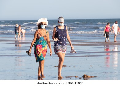 Punta Umbria, Huelva, Spain - August 2, 2020: Two women walking by the beach wearing protective or medical face masks. New normal in Spain with social distancing