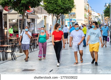 Punta Umbria, Huelva, Spain - July 10, 2020: People walking by street Calle Ancha in Punta Umbria village wearing protective mask due to covid-19. New normal in Spain