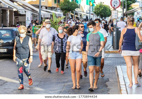 Punta Umbria, Huelva, Spain - July 3, 2020: People walking by calle Ancha street wearing protective mask due to covid-19.