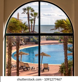 Punta Umbria, Spain. Circa April 2018. View of beachside pool area in Barcelo Punta Umbria beach resort hotel in Punta Umbria, Huelva, seen from lobby window.