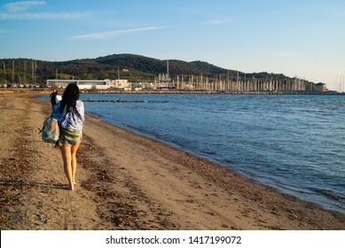Puntone Scarlino, Maremma Tuscany, Italy - circa April 2019 - Mature woman walking on the beach at sunset