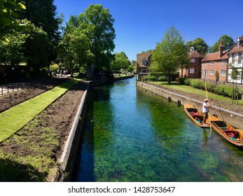 Punts with boatsman on the clear blue waters of the Great Stour river next to Westgate towers on a sunny Summers day under a blue sky.  Canterbury, Kent UK. July 8th 2018.