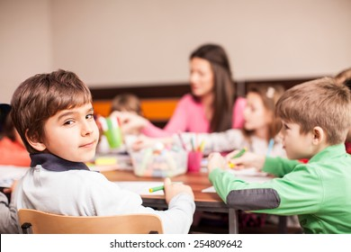 Pupil boy sitting together with his friends, boys and girls around the table in classroom and drawing. With them is their young and beautiful teacher. Boy looking at camera and smiling.