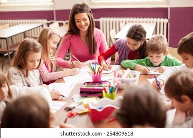 Pupil boys and girls sitting together around the table in classroom and drawing. With them is their young and beautiful teacher. She teaches children and smiling