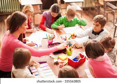 Pupil boys and girls sitting together around the table in classroom and drawing. With them is their young and beautiful teacher. She teaches children and is smiling