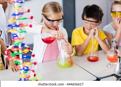 Pupil doing science while classmates looking her in classroom