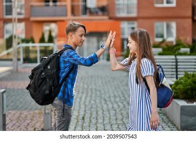 Pupil friends greeting near school with backbacks.