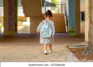 Pupil kid going to school in first class with holographic schoolbag or satchel, child walking to school bus. Toddler first day at school or preschool.