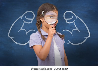 Pupil looking through magnifying glass against blue chalkboard