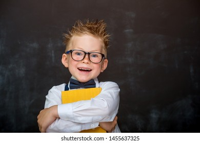 Pupil of primary school with book against chalkboard dreams to be a businessman. Nerd school boy in glasses smiling. Strong, confidence, success, possible, innovation. Go back to elementary school