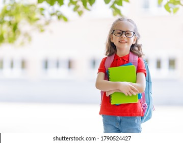 Pupil of primary school with book in hand. Girl with backpack near building outdoors. Beginning of lessons. First day of fall.