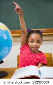 Pupil raising her hand during class at elementary school